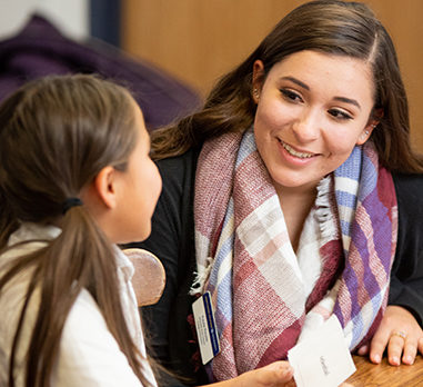 A smiling young woman speaks to a child in a classroom
