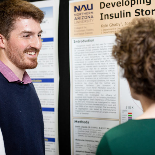 A young man presents his research to an interested listener