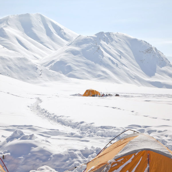 A bright orange tent in an arctic setting