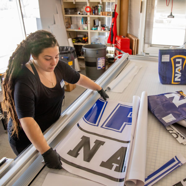 A woman measures an NAU banner on a worktable