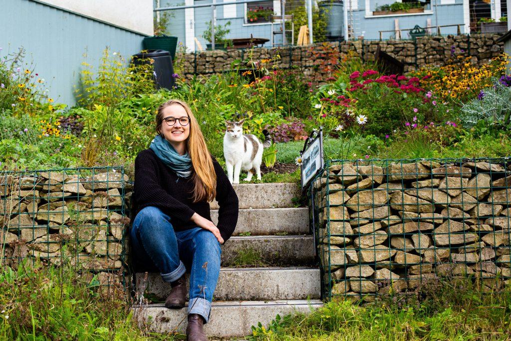 Susanna Dart at a flower garden with a cat