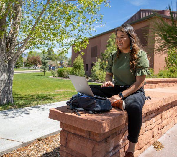Jayne sitting in front of her laptop at NAU campus