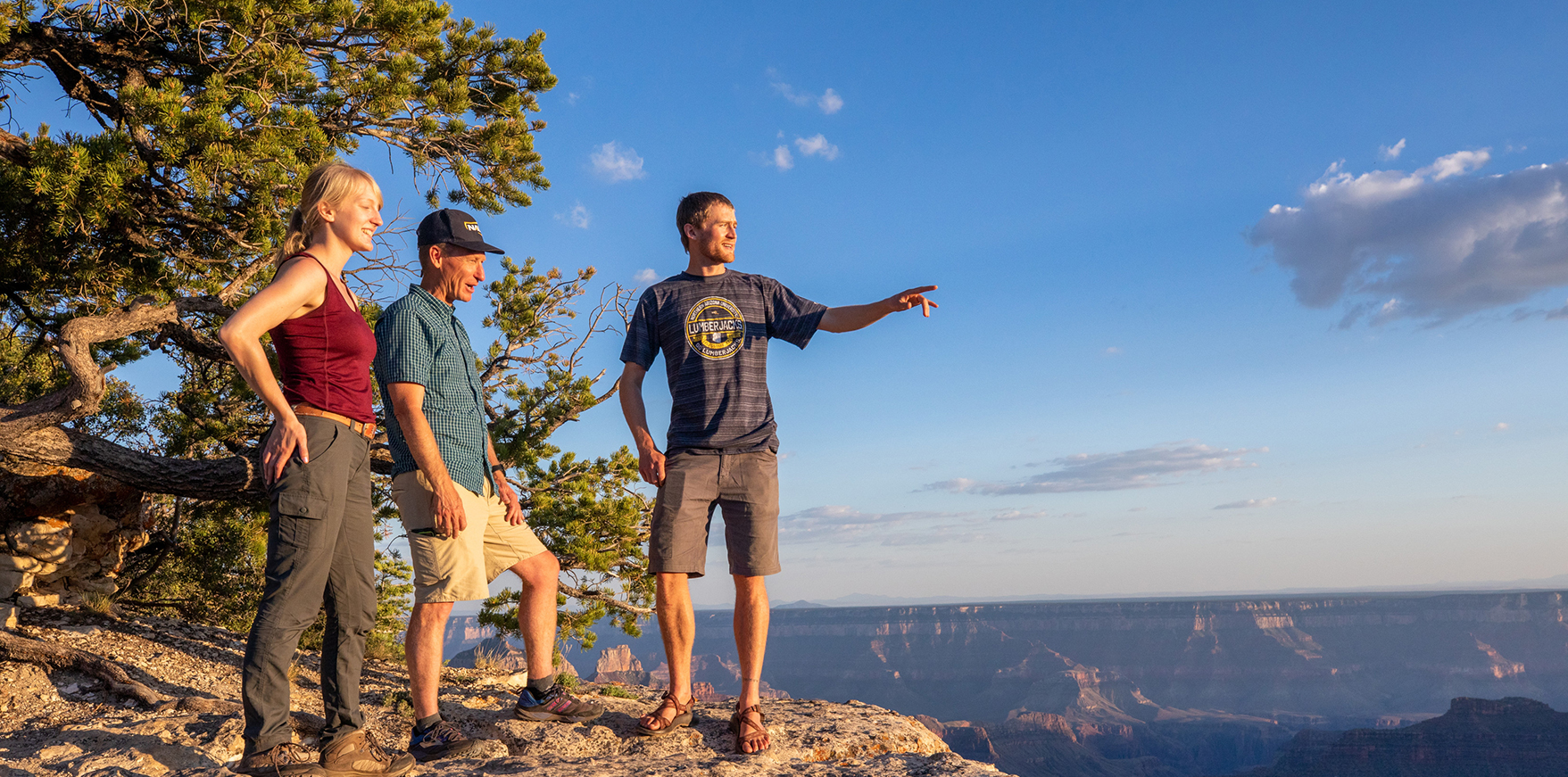 Two students and professor at the Grand Canyon pointing out over the rim