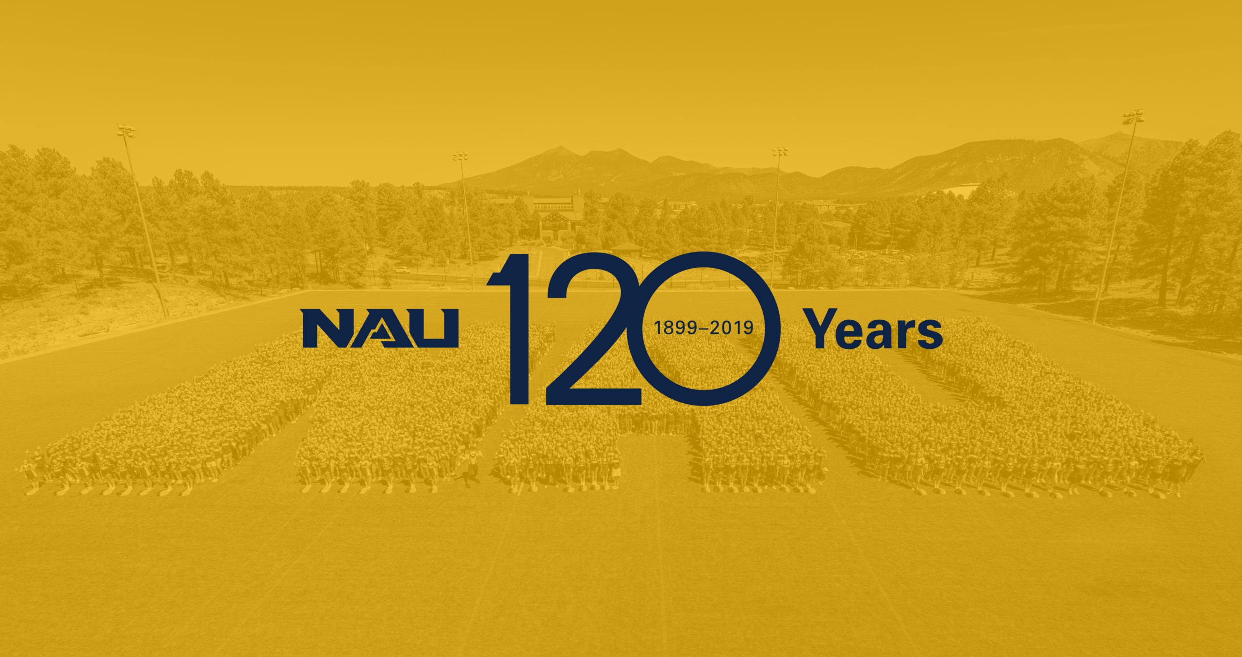 Text reading 'NAU 120 Years, 1899-2019' over an image of students forming the letters 'NAU' in a large open field