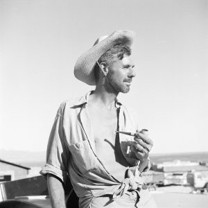 [Tad Nichols with straw hat and corncob pipe - Part of Cliff Dwellers Lodge in background; this image appears in Tad's Glen Canyon book on the title page.]