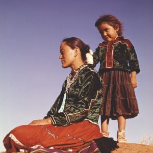 Profile of Young Navajo Mother and Child, Navajo Indian Reservation, Arizona. Wearing their traditional costume, they become part of the fascination of this redrock land. [Photographer's caption]