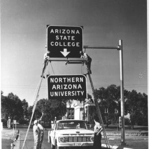 Changing of sign on the entrance sign, May, 1966.