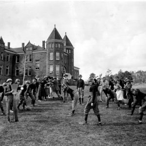[Girls' High Jinks: Group of young women dressed in football uniforms and as men along with two men, in front of the Old Main-Ashurst buildings, Northern Arizona Normal School]