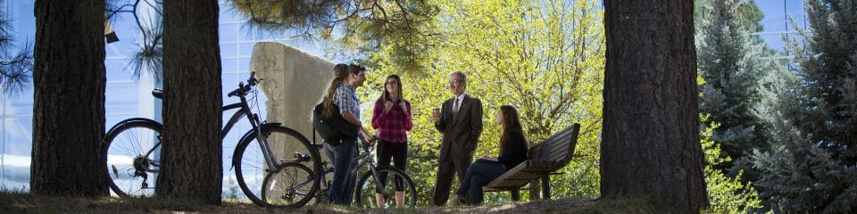 nau cefns students talk with instructor outside by trees