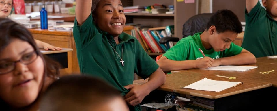 smiling student wearing a green shirt eagerly raises hand in classroom