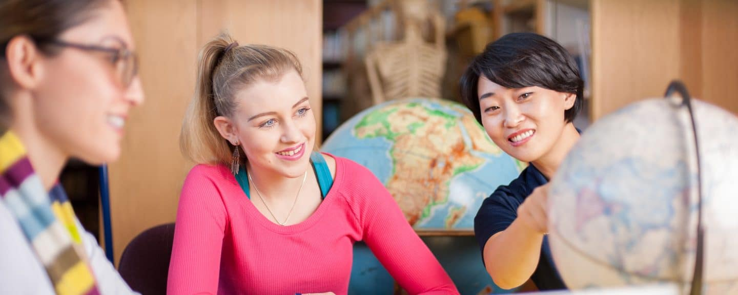 Two nau coe students interacting with an instructor using a globe