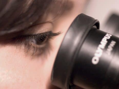 student looking through the lens of a microscope