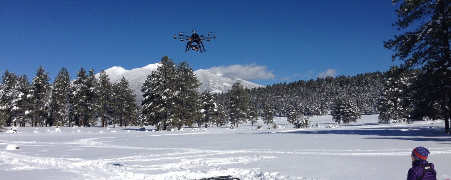 Drone in flight over snowy prairie.