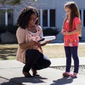 coe student at nau speaks with small child