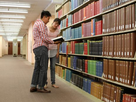 librarian with student in book stacks