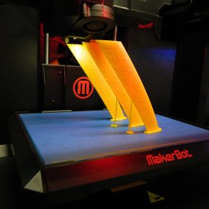 3D printing of three yellow pillars angled to the left at NAU's Cline Library.