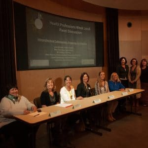 Faculty panelists and panel organizers in front of the auditorium at the Interprofessional Collaboration Panel