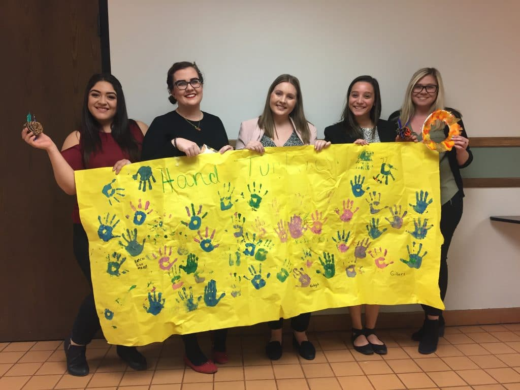 Social Work 423 students showing off creative projects made by elementary students at Killip Elementary Thanksgiving Carnival.