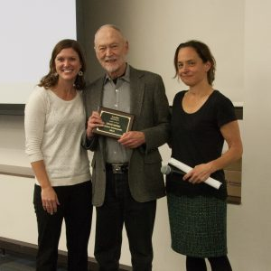 Professor David McKell stands with his NASW Lifetime Achievement Award, between presenters Katherine Mommaerts (left) and Melissa Riggs (right)