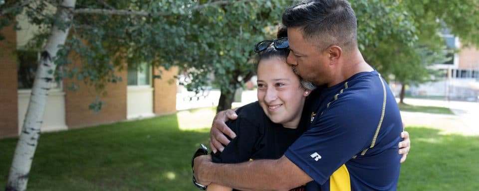 An NAU parent kisses his daughter during move-in.