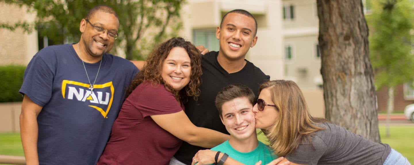 Diverse family group hugging during move in day
