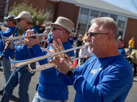 Alumni men playing trumpets at a parade