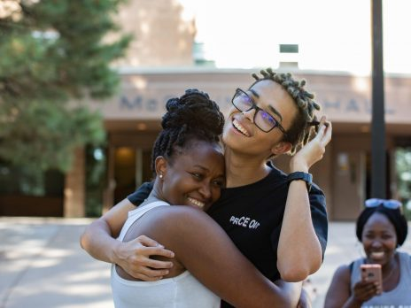 Two students hugging and smiling