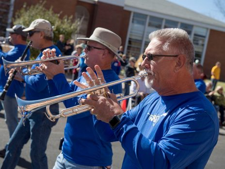 Alumni men playing trumpets in a parade
