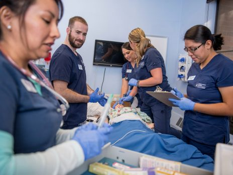 Multiple NAU Nursing students are practicing in a clinical lab.