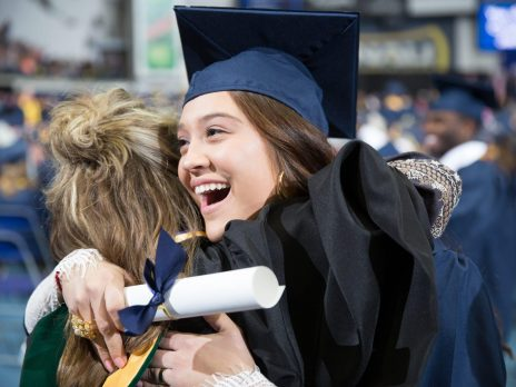 NAU Nursing graduate hugging a fellow graduate.