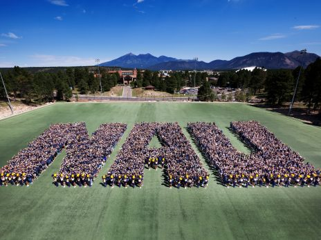 Hundreds of students standing on a field in a formation that spells NAU