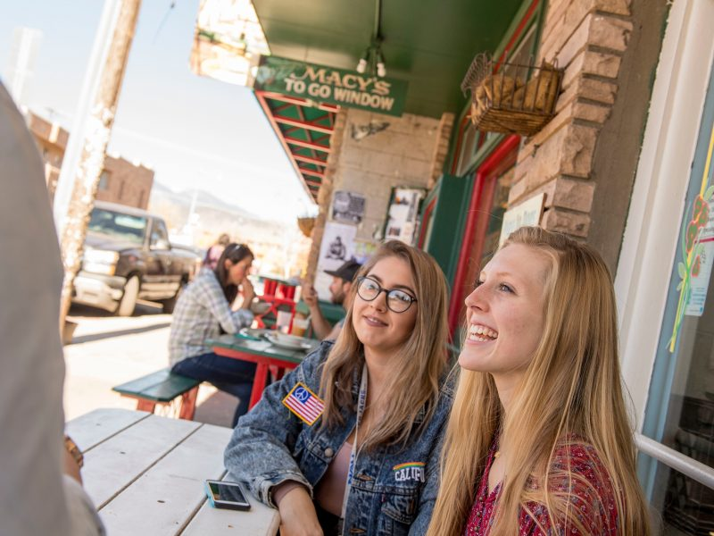 two female students smile sitting at a picnic table outside a local establishment in flagstaff
