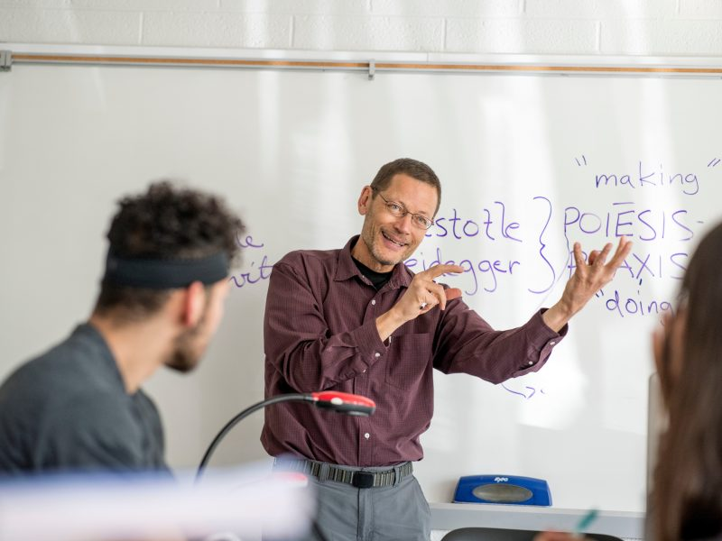 a philosophy professor smiles as he lectures his class