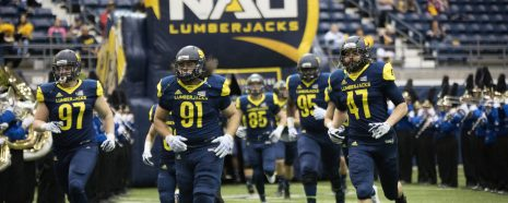 NAU football players run onto the field on Homecoming