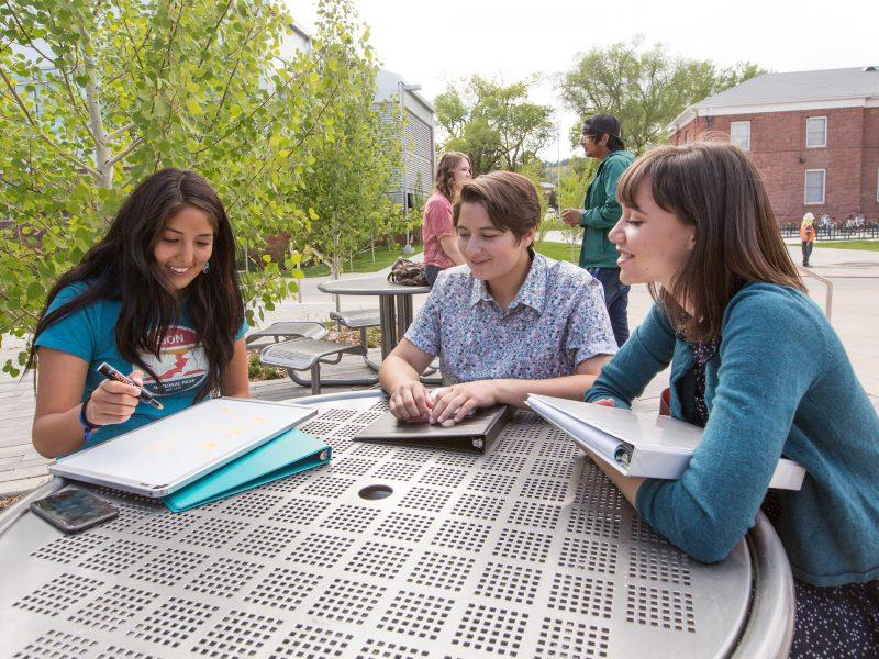 NAU students meet at an outdoor table