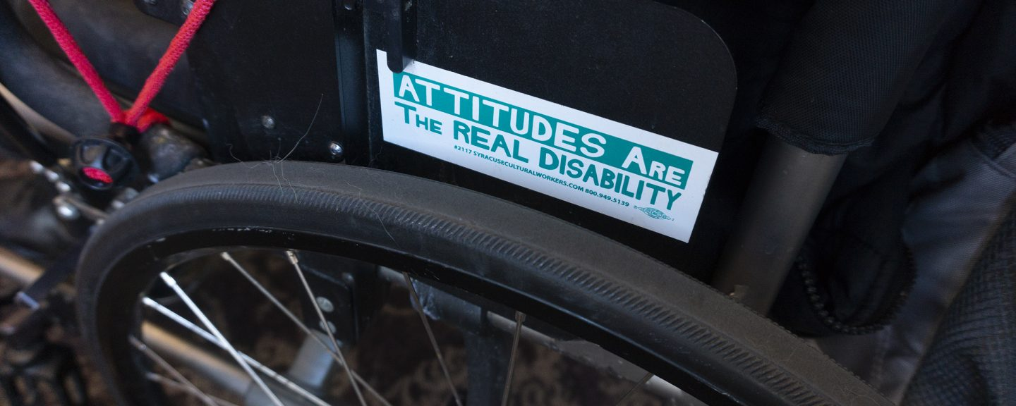 Wheelchair with a bumper sticker that states Attitudes are the Real Disability