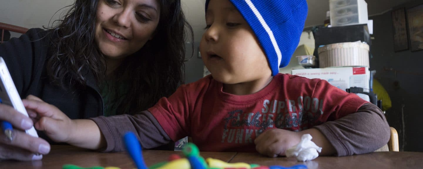 A child receiving services through IHD interacts with an app on a phone while his service provider looks on