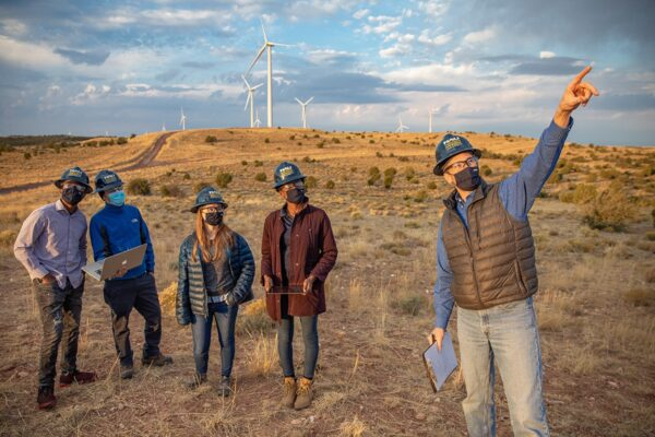 Faculty researcher and students doing research at wind farm.