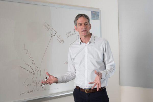 Scott Goetz standing in front of a whiteboard