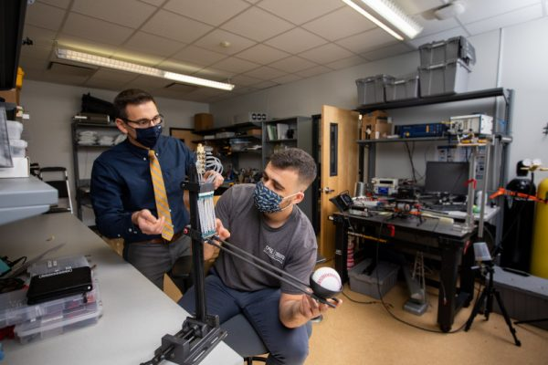 Michael Shafer and graduate student Diego Higueras-Ruiz conducting a visual inspection of their new compliant robotic arm actuated with cavatappi artificial muscles