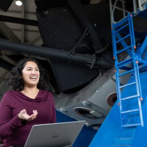 Cristina Thomas standing in front of the Discovery Channel Telescope in Happy Jack, AZ
