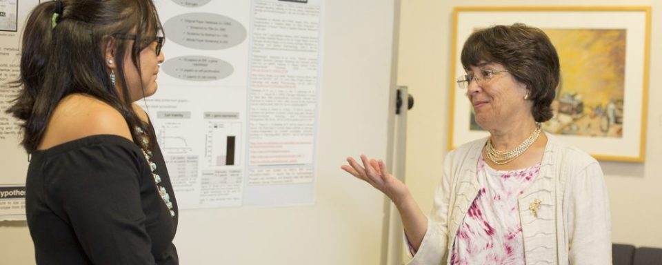 Catherine Propper discussing a research poster with a student