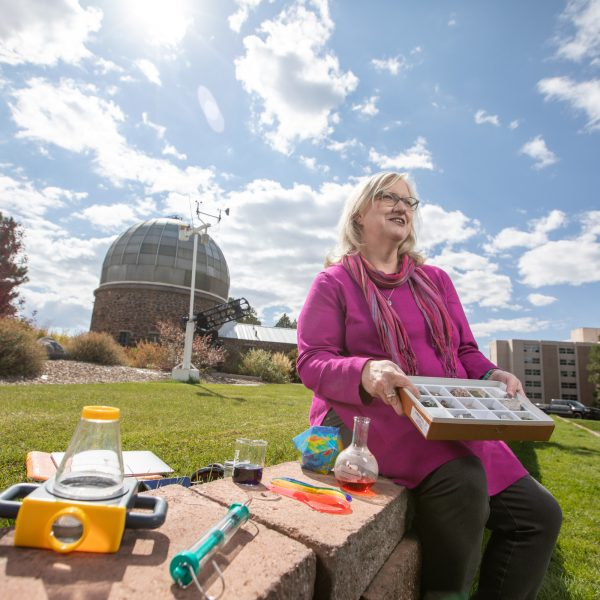 Marti Canipe sitting outside of the Lutz telescope with science teaching tools
