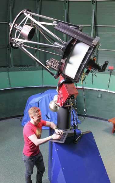 Colin Chandler standing by the Lutz telescope