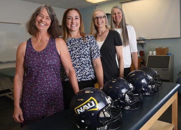 Heidi Wayment, Ann Huffman, Deborah Craig, Monica Lininger standing by NAU football helents