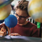 a student sits at a desk surrounded by model planets and looking concentrated