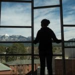 nau student staring out a window looking at the San Francisco peaks
