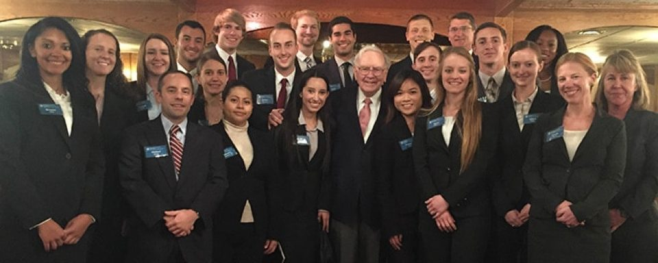 Group of 18 diverse business students gathered around Mr. Warren Buffett during their 2015 visit.