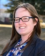 Female college student with long brown hair and glasses, wearing a multi-colored shirt and blazer.