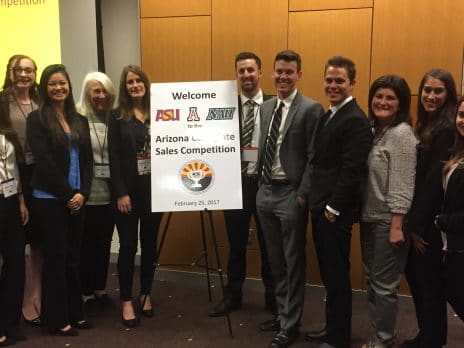 A group of college students in business casual clothes stands by a sign that says Welcome to the Arizona Collegiate Sales Competition. The group is made up of 8 women and 5 men.